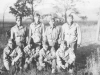 Eight soldiers pose for a photograph in the forest. [Courtesy of Mary Hamasaki]