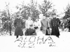 """Soldiers and Wisconsin women pose for a group photo in front of the snowman and sign """"Aloha '42  100 INF. BN. [Courtesy of Goro Sumida]"""