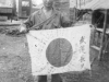 Tom Matsumura holds an enemy sword and flag while stationed in the Philippines. [Courtesy of Florence Matsumura]