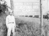 Tom Matsumura stands in front of a sign at Camp McCoy, Wisconsin. [Courtesy of Florence Matsumura]